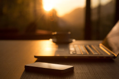 stock-photo-82454689-computer-coffee-mug-telephone-on-black-wood-table-sun-rising